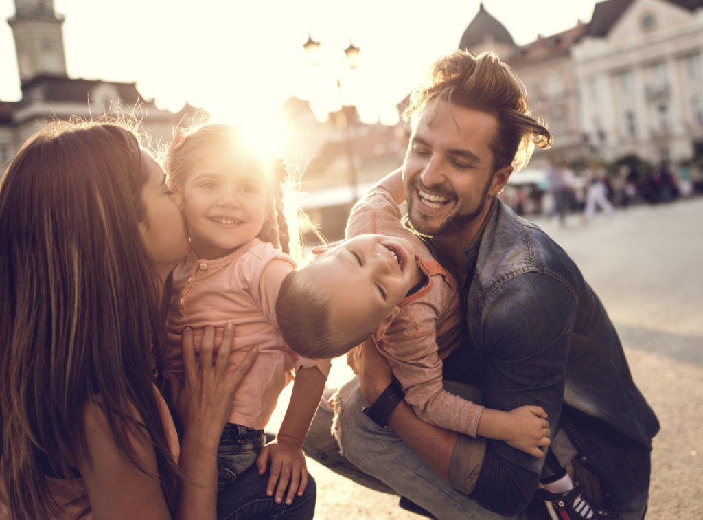 Happy parents enjoying with their small children in the city at sunset.